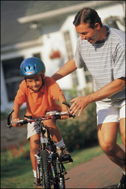 Dad and Son Learning to Ride Bicycle